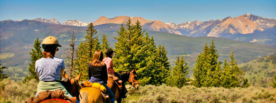 group on horses, overlooking mountains