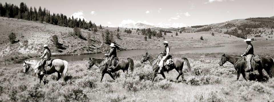 black & white photo of four horseback riders